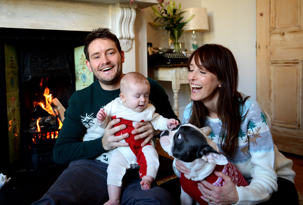 Portrait professional in London catches the fun and merriment for this family as they sit around the fire with the per dog