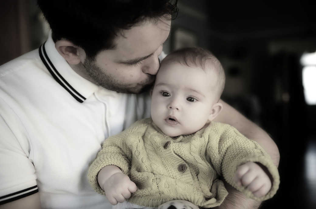 Portraiture photography in London of a father lovingly kissing his baby daughter in Dulwich at their family home