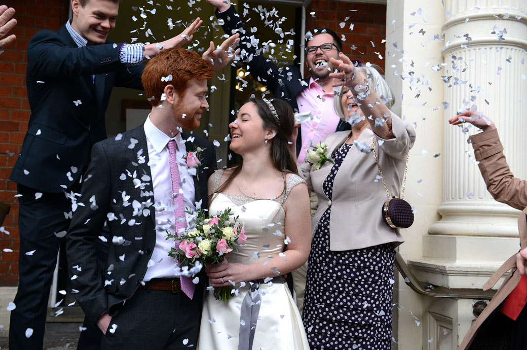 The newlywed couple enjoying the confetti throwing fun in this lively wedding photo taken at London Wedding venue Mayfair Library outside on the front steps