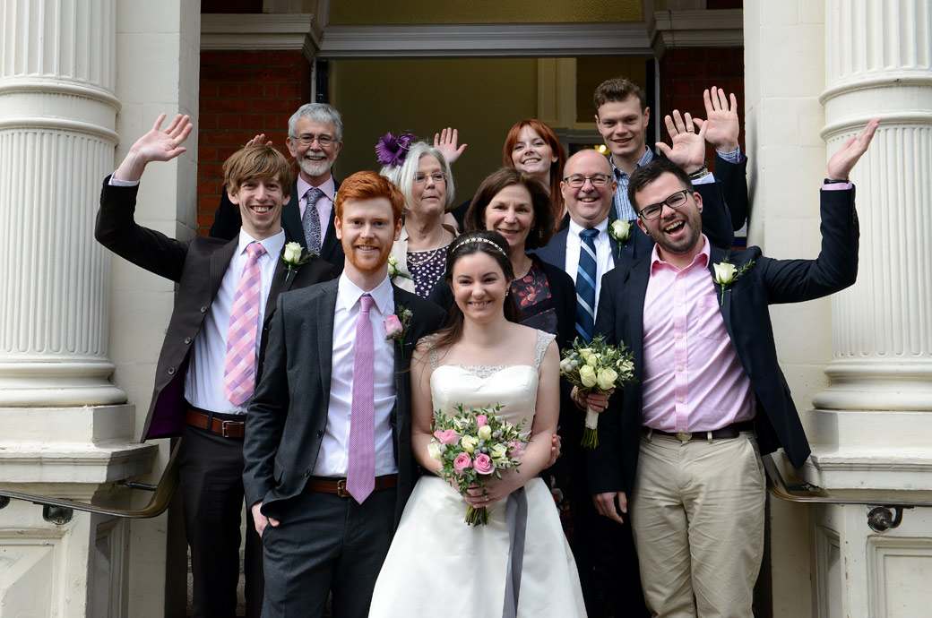 Everyone waving in this small family group wedding picture taken on the steps of Mayfair Library a popular London wedding venue alternative to Westminster Register Office