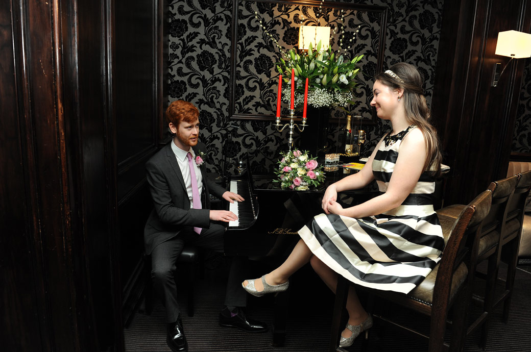 The Groom plays the piano for his Bride in this fun wedding picture captured in the comfortable Pine Bar of the Millennium Hotel a London wedding venue with a touch of class