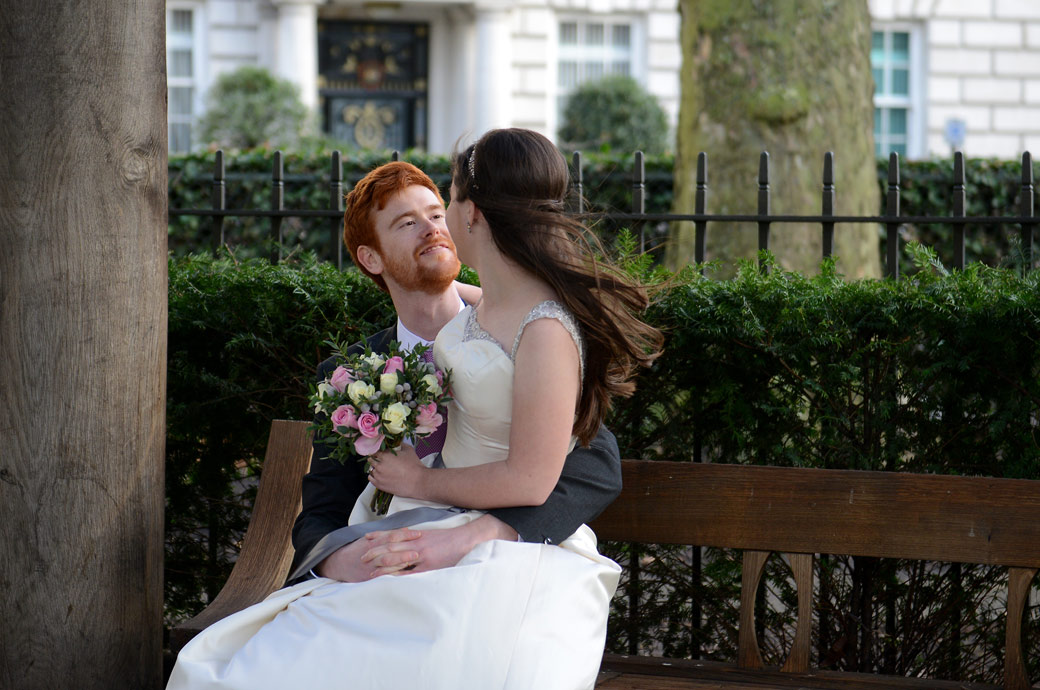 A happy groom looks loving into the eyes of his Bride captured in this romantic wedding photo taken opposite London wedding venue Millennium Hotel in Grosvenor Square Garden