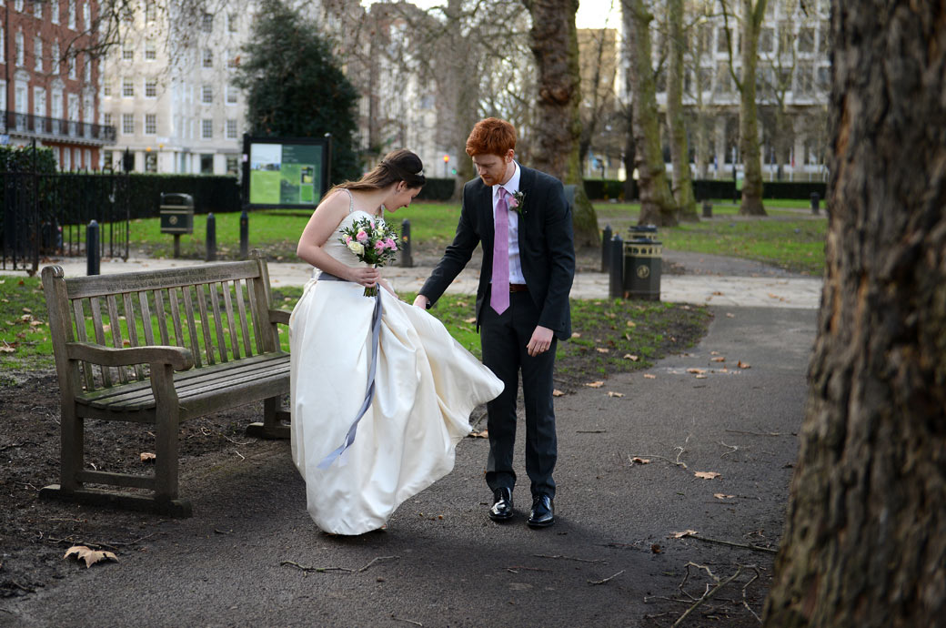 Groom helps his bride  with her dress in this wedding picture captured as they walk into Grosvenor Square Garden opposite London wedding venue the Millennium Hotel