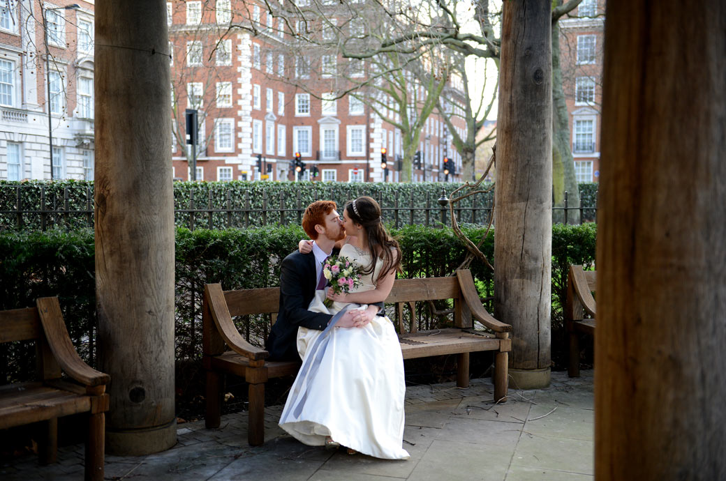 Wedding picture of a Bride and Groom on a bench in Grosvenor Square Garden opposite the plush London wedding venue The Millennium Hotel having a romantic kiss