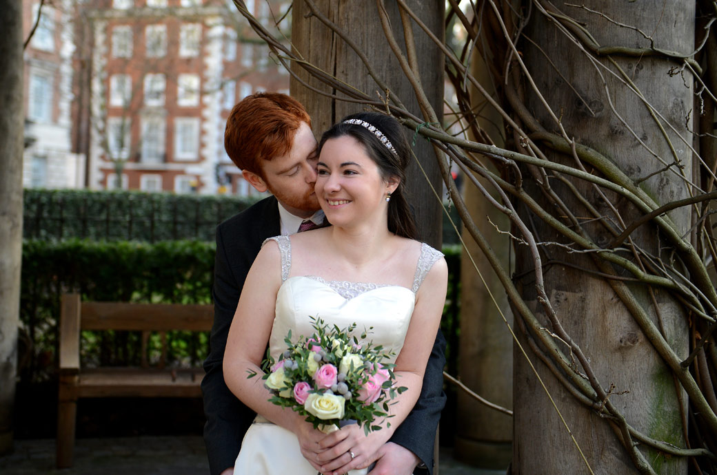 A smiling Bride and a loving kiss captured in Grosvenor Square Garden opposite London wedding venue The Millennium Hotel in this romantic wedding photograph