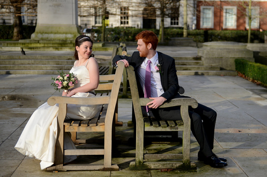 Newlyweds sitting on park benches look over to each other in this fun wedding photograph from Grosvenor Square Garden opposite London wedding venue the Millennium Hotel