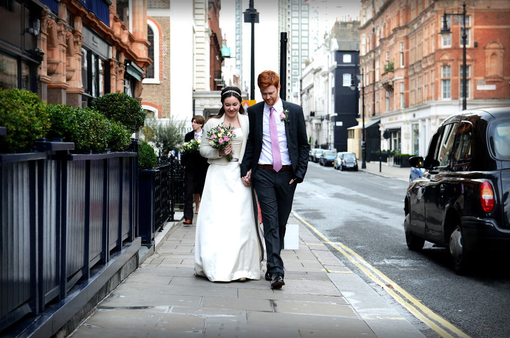 Bride and Groom leading the way in this wedding photograph taken as they walk from Mayfair Library to the reception at the Millennium Hotel, Grosvenor Square, London