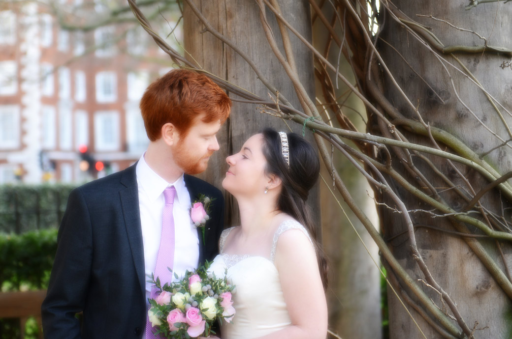 Romantic soft focus wedding photo of the newlyweds looking into each other's eyes in Grosvenor Square Garden opposite the Millennium Hotel a fine London wedding venue