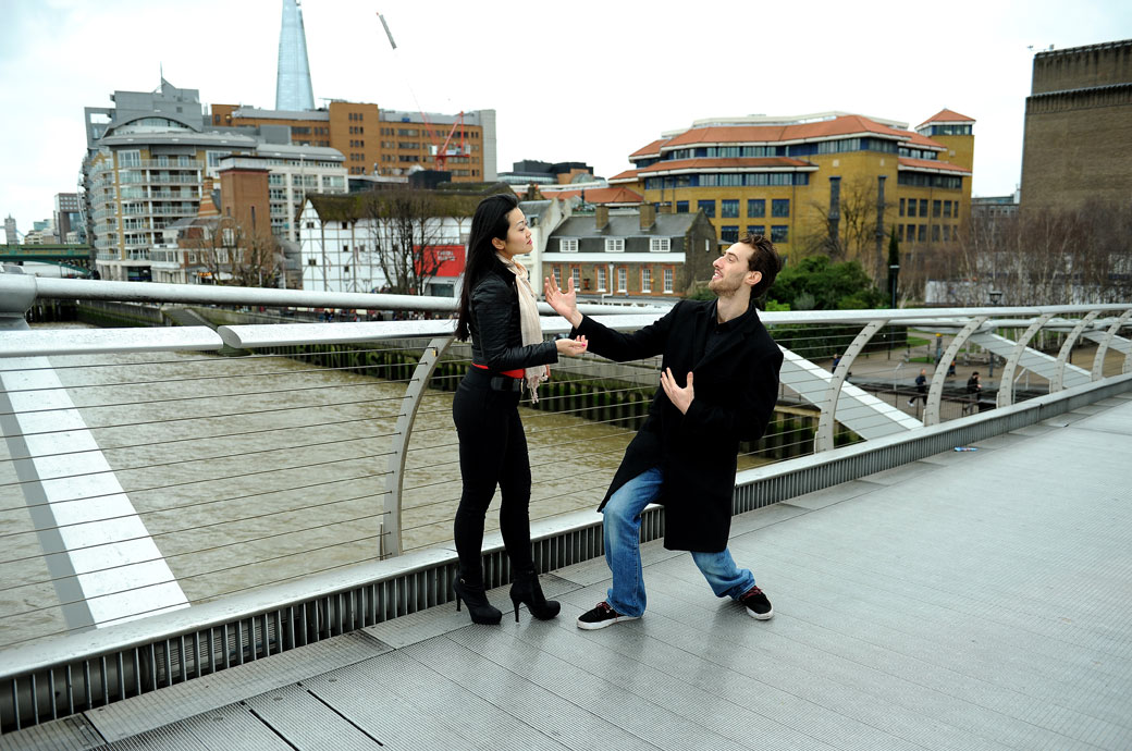 Thespian couple act out Romeo and Juliet on the Millennium Bridge in front of The Globe Theatre in this fun London pre wedding photo