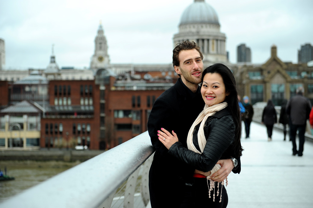 Smiling couple standing on the Millennium Bridge in London captured in this pre wedding shoot photograph with St. Paul's Cathedral in the background