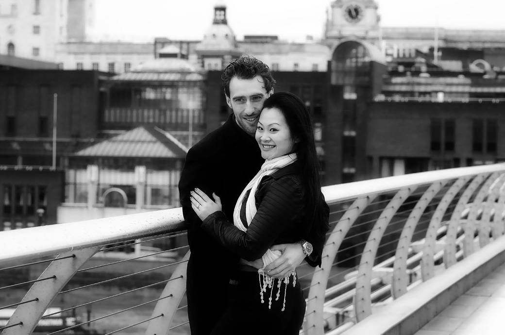 Lovers watch the world go by as they embrace in this pre wedding photo taken on the Millennium Bridge in London