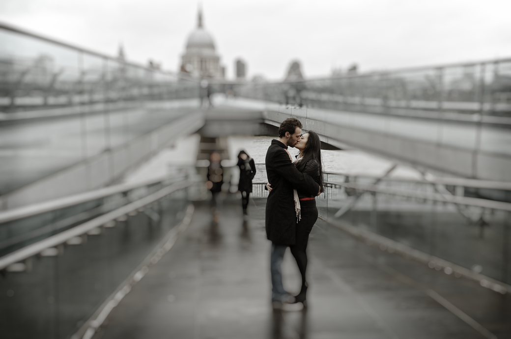 Romantic kiss captured in this dramatic pre wedding photograph taken on the ramp of the London Millennium Bridge with St. Paul's Cathedral in the background