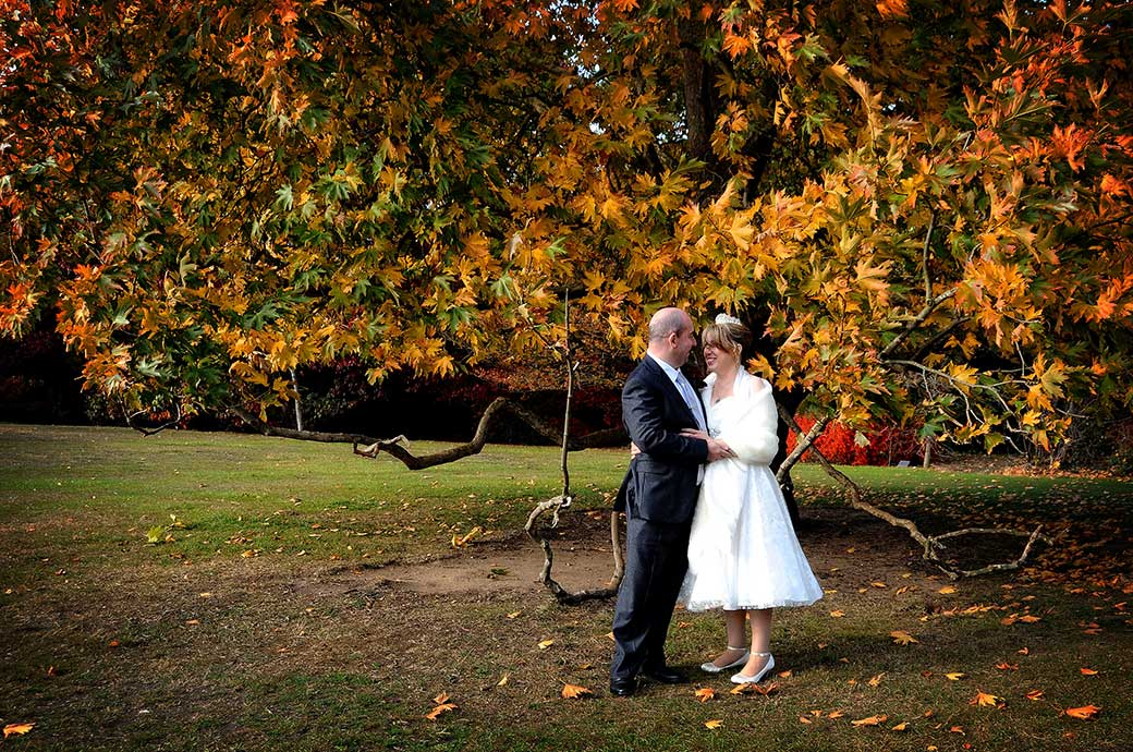 A romantic and beautifully colourful autumnal wedding photograph captured on the lawn at the luxurious London wedding venue Cannizaro House based on the edge of Wimbledon Common
