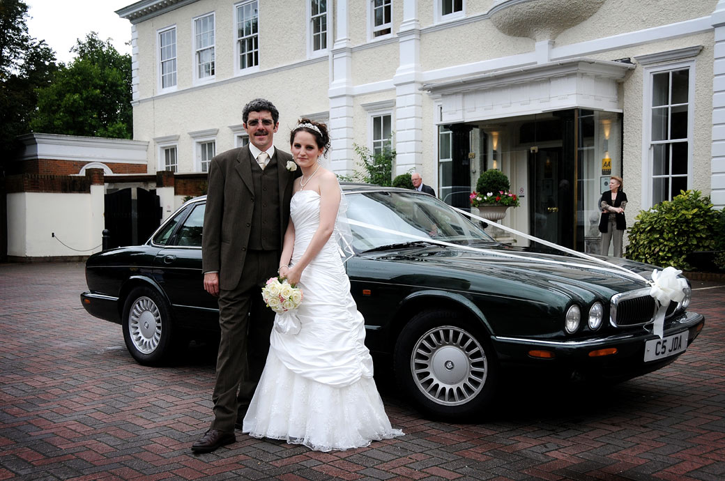 Smiling Bride poses with her father for a wedding photo in front of their Jaguar at London wedding venue Cannizaro House before leaving for her marriage at Fulham Palace London