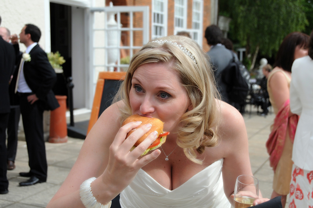 Bride grabbing a bite of a burger in this fun wedding picture captured on the terrace at London wedding venue Cannizaro House in Wimbledon London