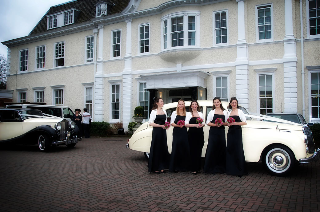 Bridesmaids standing with their bouquets in front of a classic cream Bentley outside the lovely London wedding venue Cannizaro House with its Queen Anne Baroque architectural style