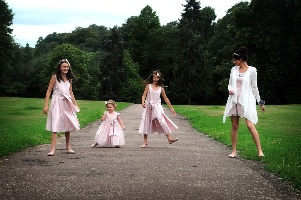Relaxed bridesmaids in pink having fun doing a funny walk along the path in this lovely summer wedding picture taken at London wedding venue Cannizaro House on Wimbledon Common