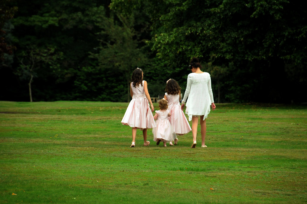 Bridesmaids walking along the lawn towards the trees in this evocative summer wedding picture taken at London wedding venue Cannizaro House