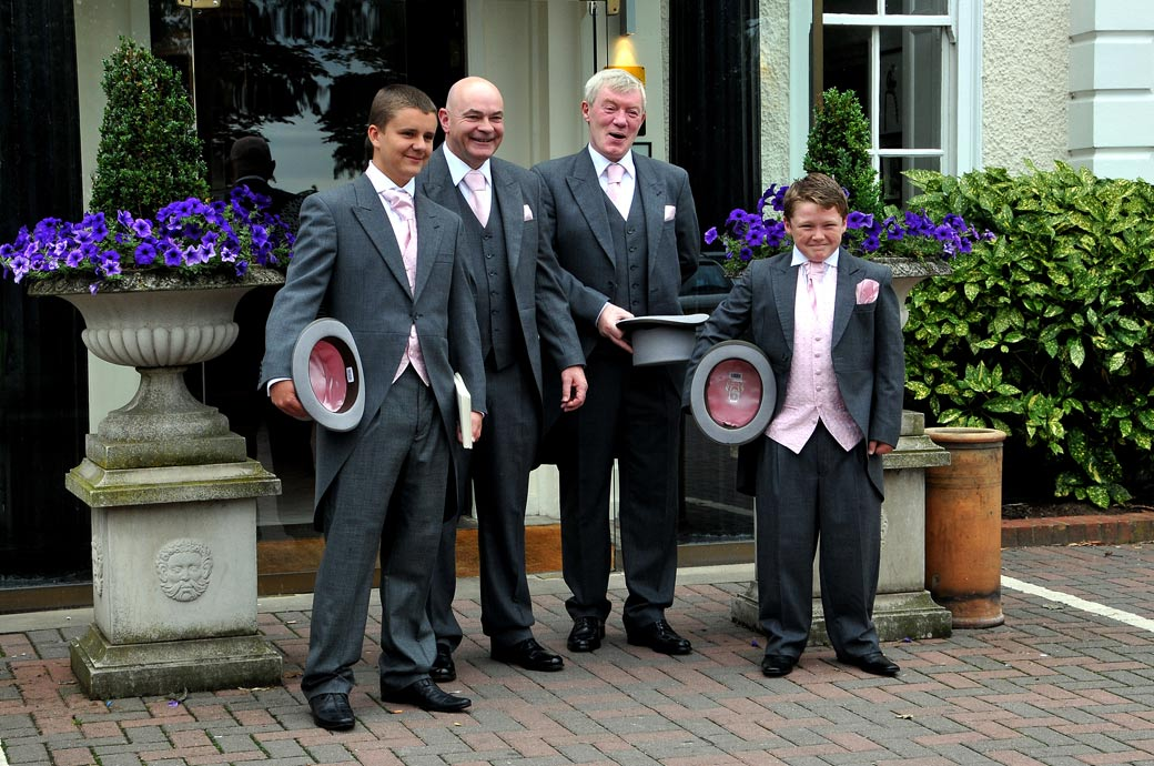 Wedding photograph taken outside London wedding venue Cannizaro House on Wimbledon Common of the Groom and Groomsmen standing ready for a picture holding their top hats