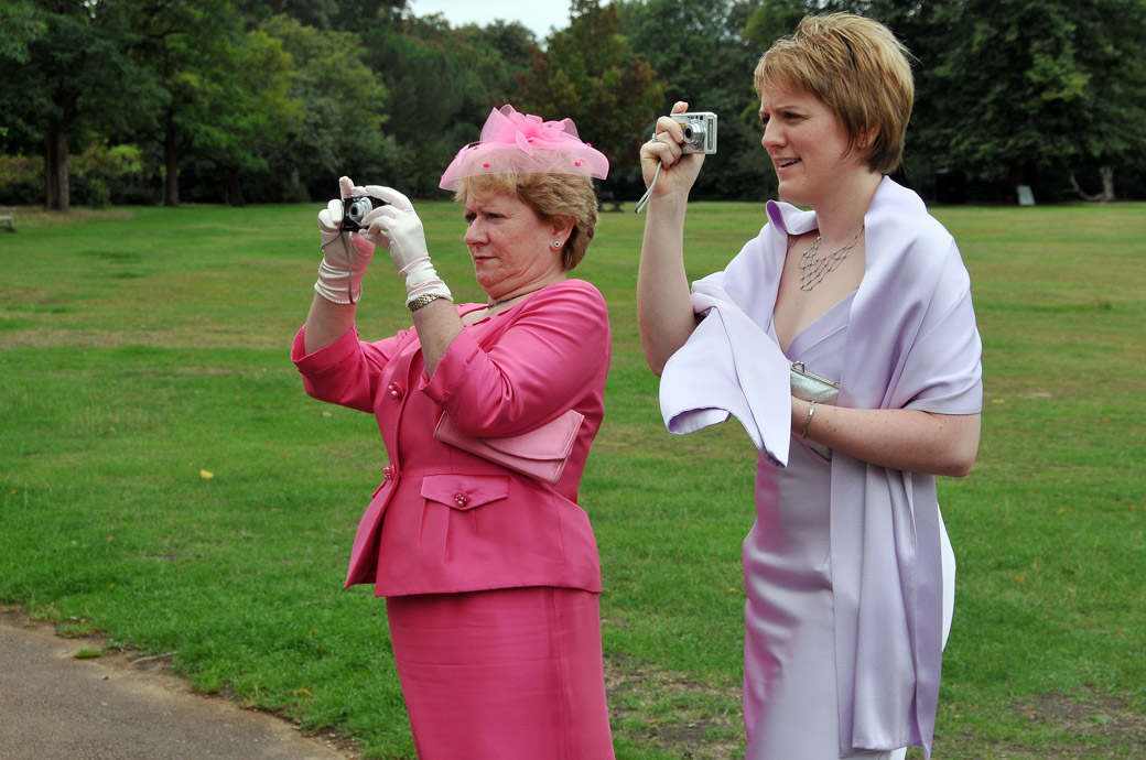 Ladies in pink and lilac concentrating taking photos in the lovely caught in the moment wedding picture taken in the gardens at Cannizaro House in Wimbledon London