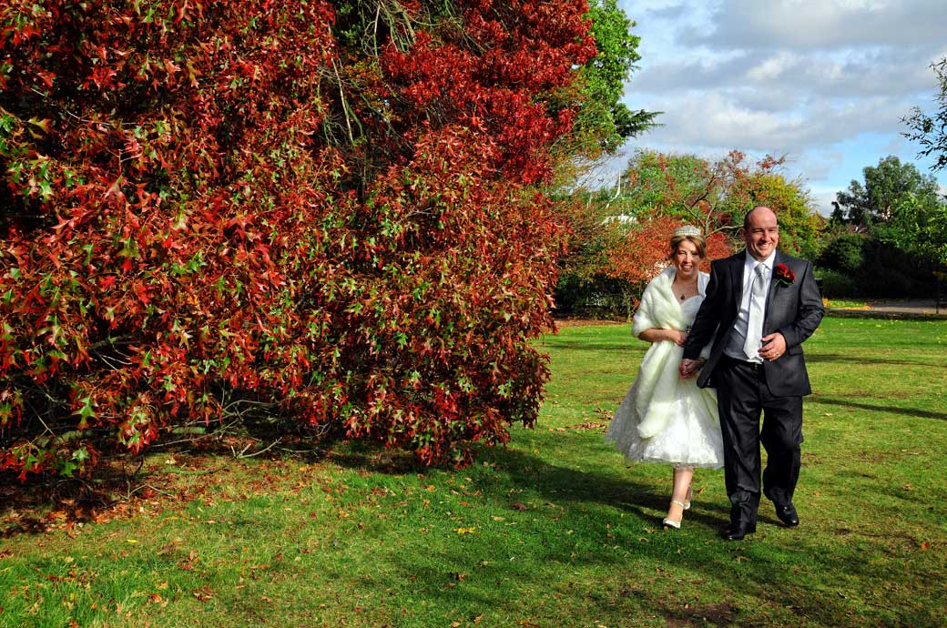 Happy couple wedding picture taken of them walking past the beautifully coloured autumnal trees in the gardens at the lovely Cannizaro House in Wimbledon