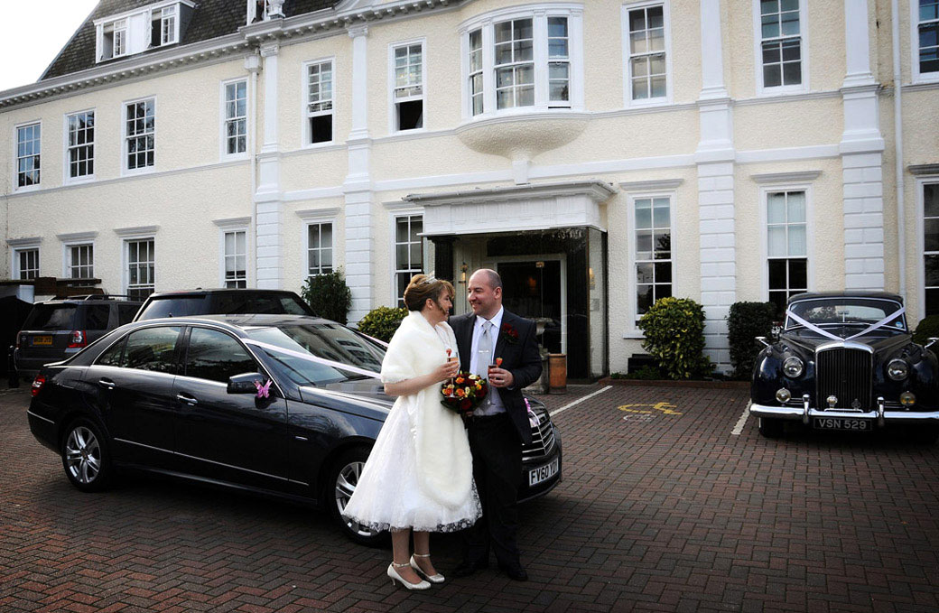 Sweet wedding photograph of a loving couple standing together by their wedding car with champagne in front of London wedding venue Cannizaro House near Wimbledon Common