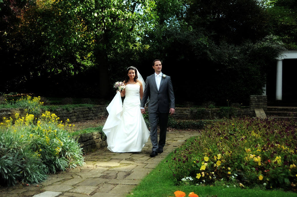 Excited romantic wedding couple wedding photo taken as they walk through the colourful sunken garden at Cannizaro House a lovely luxury London wedding venue in Wimbledon