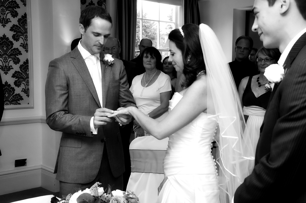 Groom carefully places the ring on his Bride's finger in this romantic wedding photograph Cannizaro House a relaxed and luxurious South West London wedding venue by the common