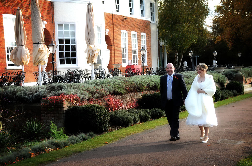 A happy Bride and Groom walking by the terrace at the lovely relaxing South West London wedding venue Cannizaro House