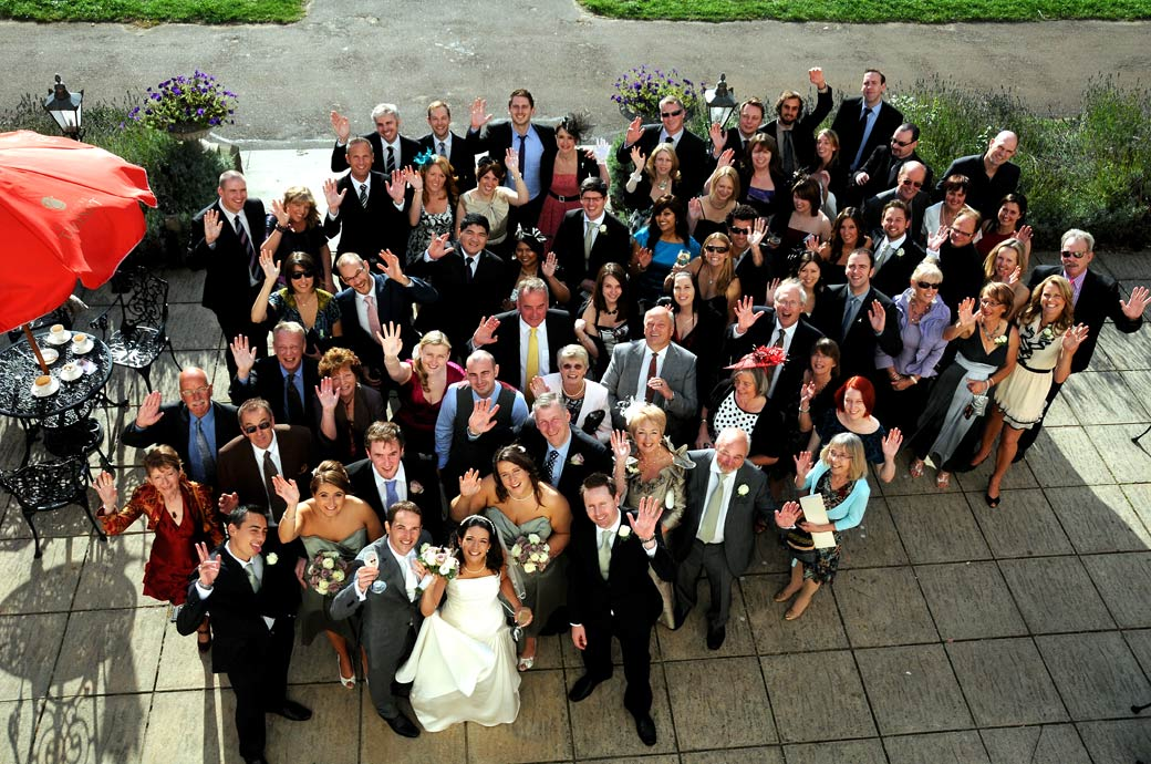 Wedding picture taken from a top floor window of happy waving wedding guests on the terrace below at the relaxed luxury London wedding venue of Cannizaro House in South West London