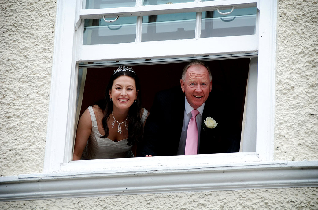 Fun wedding photo of the Bride and her father with their heads poking out through the window checking on the waiting Bridesmaids at Cannizaro House Wimbledon London