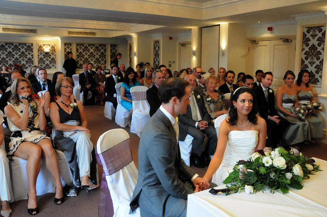 A lovely sweet wedding picture taken at Cannixaro House in Wimbledon London of a content and smiling Bride looking to the registrar as the Groom holds her hand