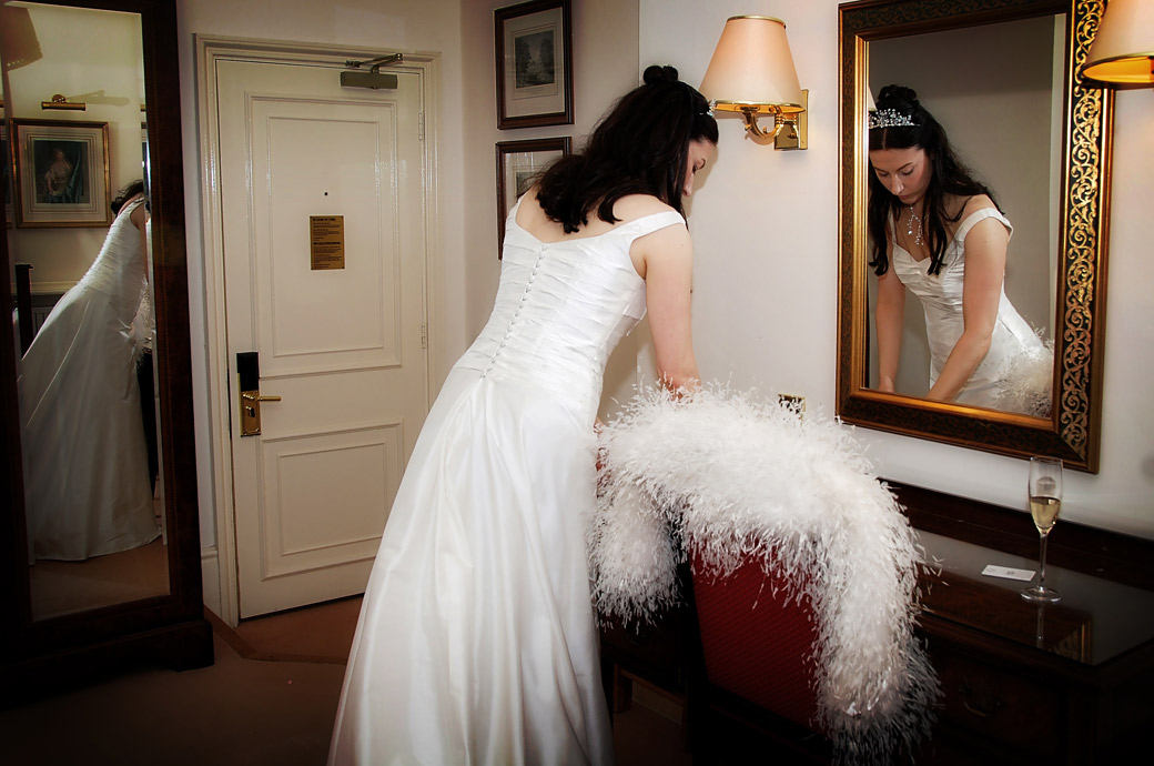 Unusual wedding photograph of a bride reflected in two mirrors as she gets ready on the morning of the big day at London wedding venue Cannizaro House