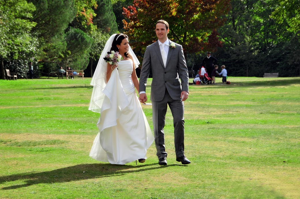 Wedding picture of a smiling Bride and Groom taken as they turn around on the lawn outside the pretty and relaxed Cannizaro House a fine London wedding venue situated near Wimbledon Village