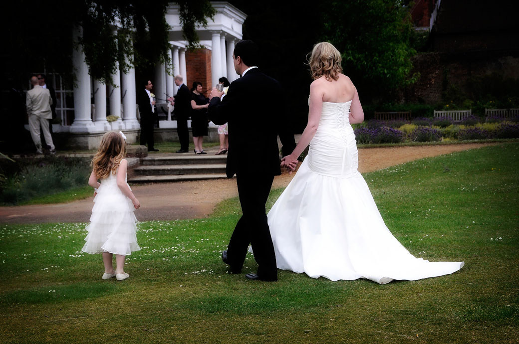Romantic wedding picture of newly-weds walking gracefully across the lawn with a bridesmaid captured at London wedding venue Cannizaro House on Wimbledon Common
