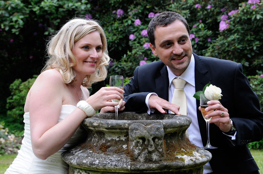 Happy wedding picture of smiling newly-weds leaning on a stone urn with glasses of champagne in the gardens at Cannizaro House in Wimbledon a fine South West London wedding venue