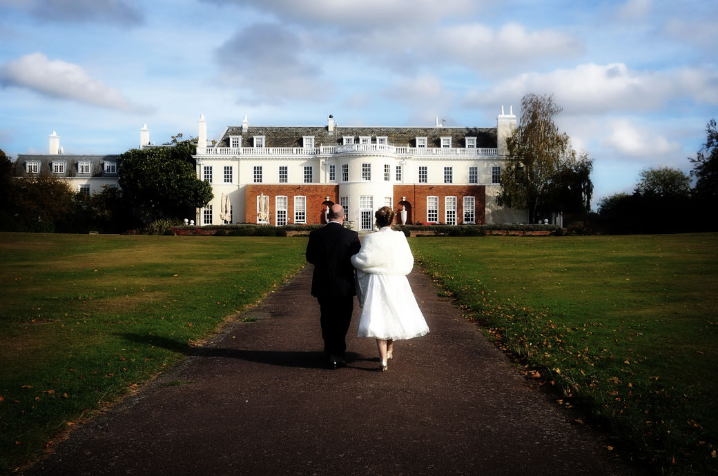 A lovely romantic wedding photograph of newly-weds peacefully walking hand in hand down the path towards Cannizaro House, Wimbledon a fine London wedding venue
