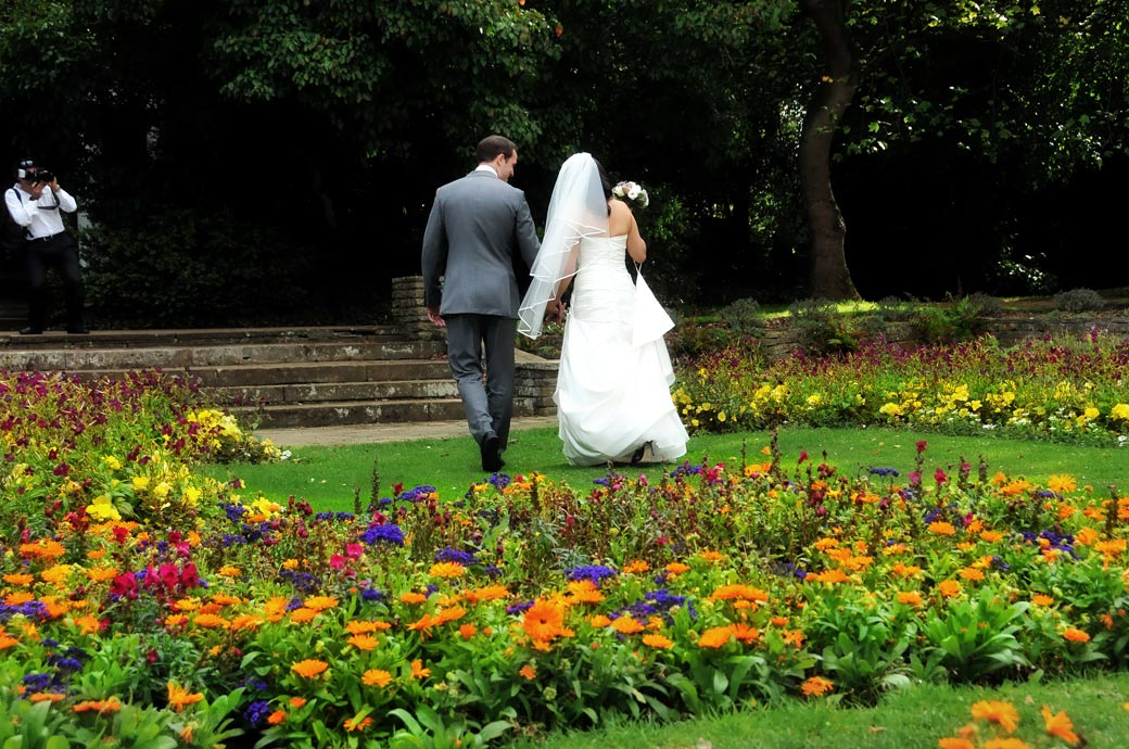 Wedding couple walking hand in hand along the grass in the colourful sunken garden in this romantic wedding photograph captured at Cannizaro House Wimbledon Common London