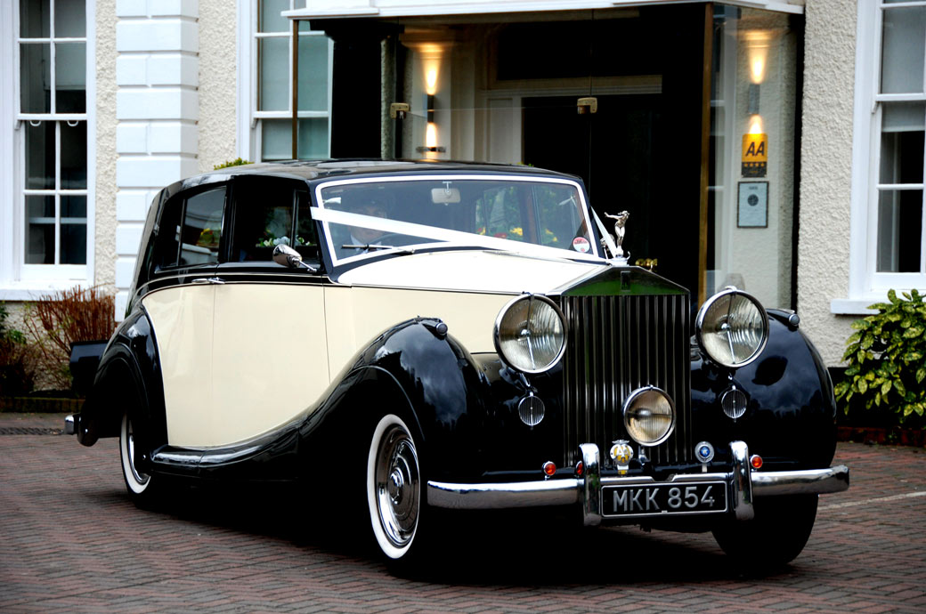 Wedding picture of a beautiful classic black and cream Rolls Royce with the Bride aboard and pulling out of the drive at Cannizaro House on route to her church wedding in London