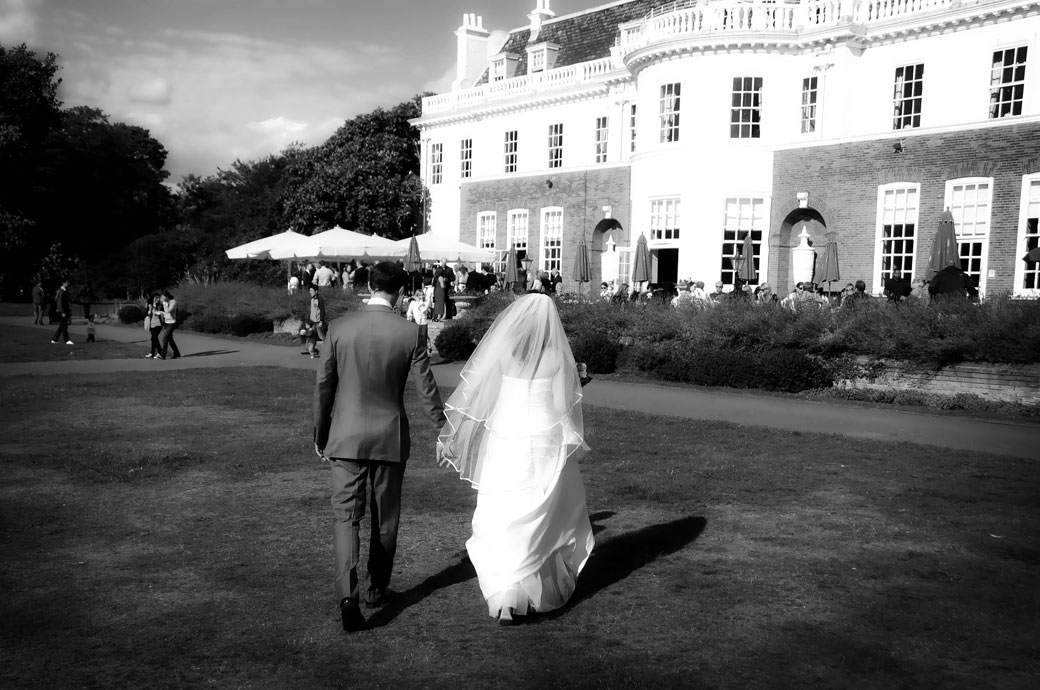 Bride and Groom walking hand in hand across the lawn towards Cannizaro House in this romantic wedding photo taken in Wimbledon