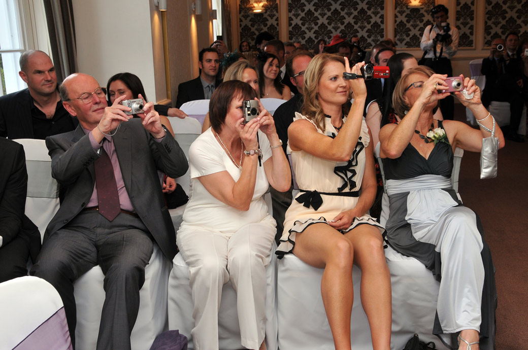 A fun wedding photo of all the guests holding up their cameras in the front row during the signing of the register in South West London wedding venue Cannizaro House