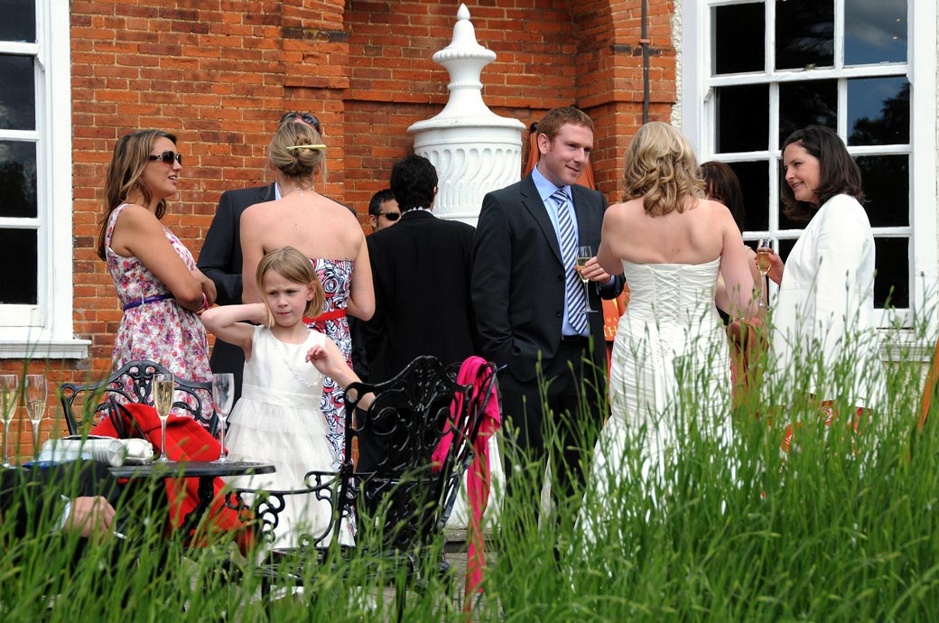 Relaxed wedding guests chatting  with the Bride over champagne in this wedding picture captured on the pleasant terrace at Cannizaro House a lovely chilled boutique London wedding venue