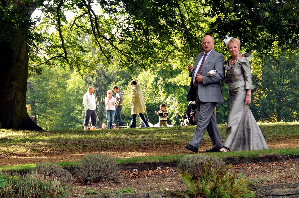Relaxed wedding guests walking past the trees in this evocative summer wedding photo taken in the gardens at the London wedding venue Cannizaro House in Wimbledon