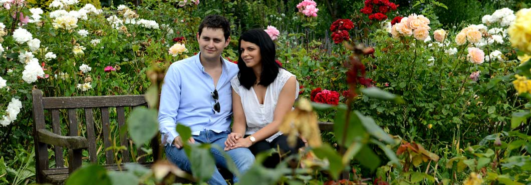 Pre wedding photograph of a romantic couple sitting on a bench in a walled Garden surrounded by wonderfully coloured blooms in the Brockwell Park London