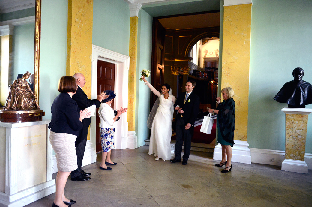 An ecstatic Bride punches the air with her bouquet wedding photograph as she leaves with her husband from her London wedding at the Little Brompton Oratory
