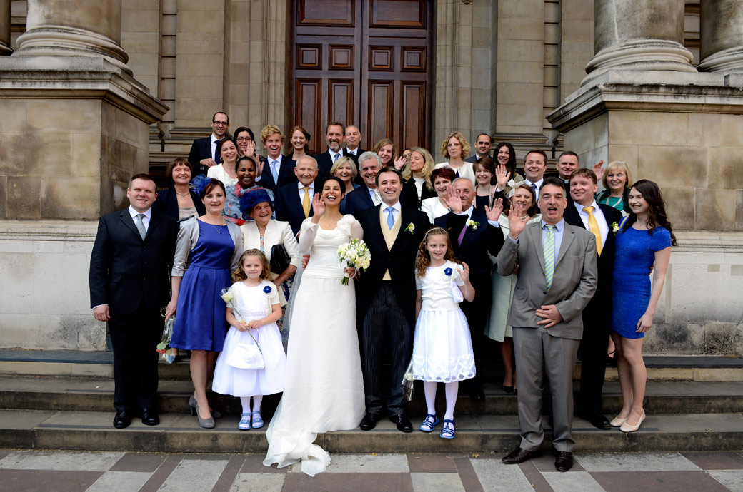 Everyone at the wedding waving wedding picture taken on the steps of the London Brompton Oratory captured by London Lane wedding photographers