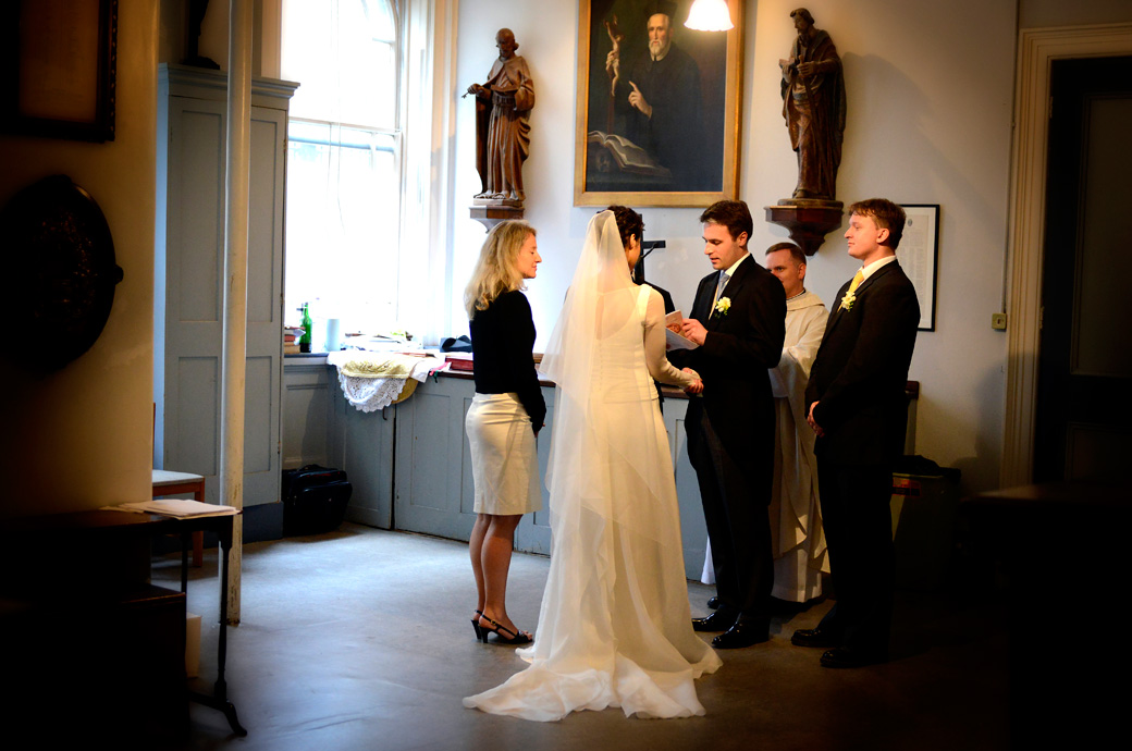 Groom repeating his vows in this atmospheric wedding picture taken In the ante-room of the Little Brompton Oratory a delightful London wedding venue