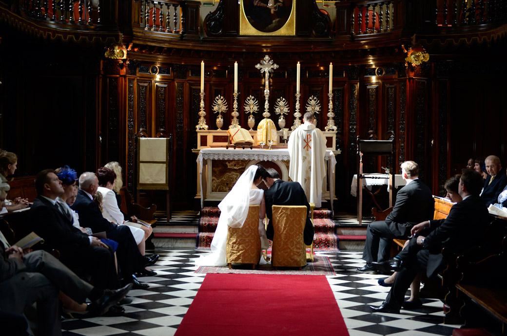 Bride and Groom Little having a little head to head in this beautiful wedding photograph taken during the wedding service at the Little Brompton Oratory in London