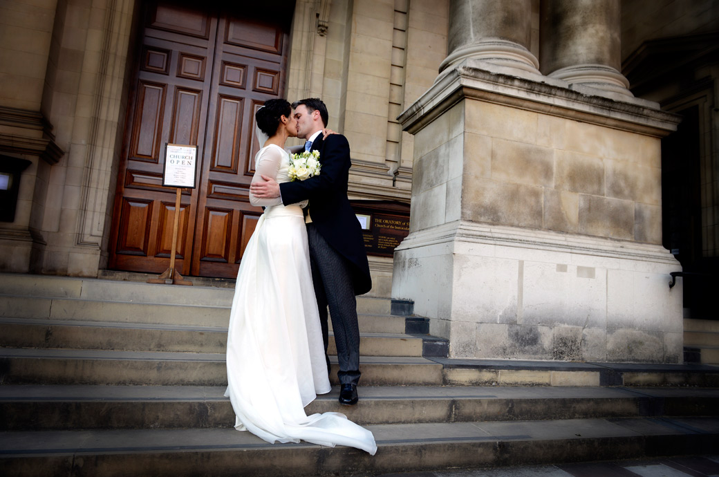 A romantic kiss on the steps wedding picture taken at the London Brompton Oratory a stunning Italian Renaissance style London wedding venue next to the V&A