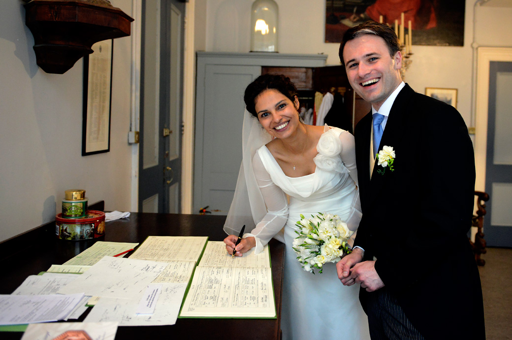 Happy beautiful Bride and Groom laughing and smiling as they sign the register wedding photo taken at the Little Brompton Oratory London wedding venue